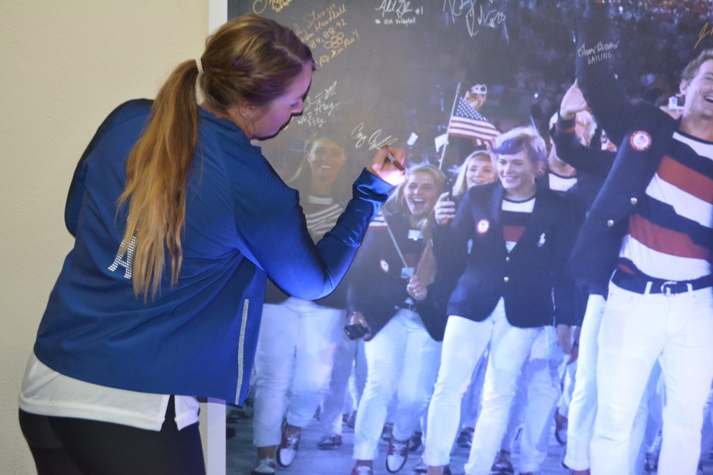 Bronze medalist in shooting Corey Cordell signs her name to the photo from the Opening Ceremony.