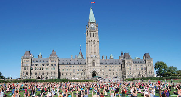 From May to December in Ottawa, Ontario, thousands of residents and visitors have the chance to participate in free yoga sessions outside the Parliament of Canada. Photo courtesy of Ottawa Tourism